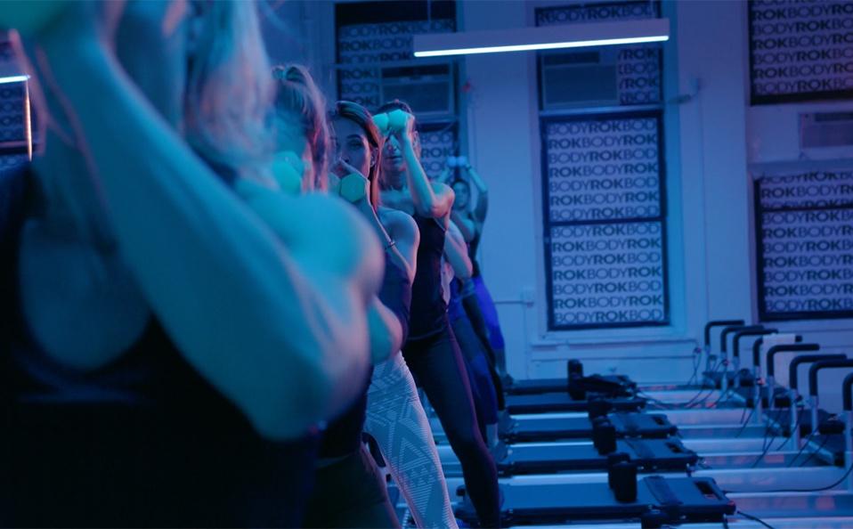 Women lift weights during Bodyrok pilates workout under Ketra blue light