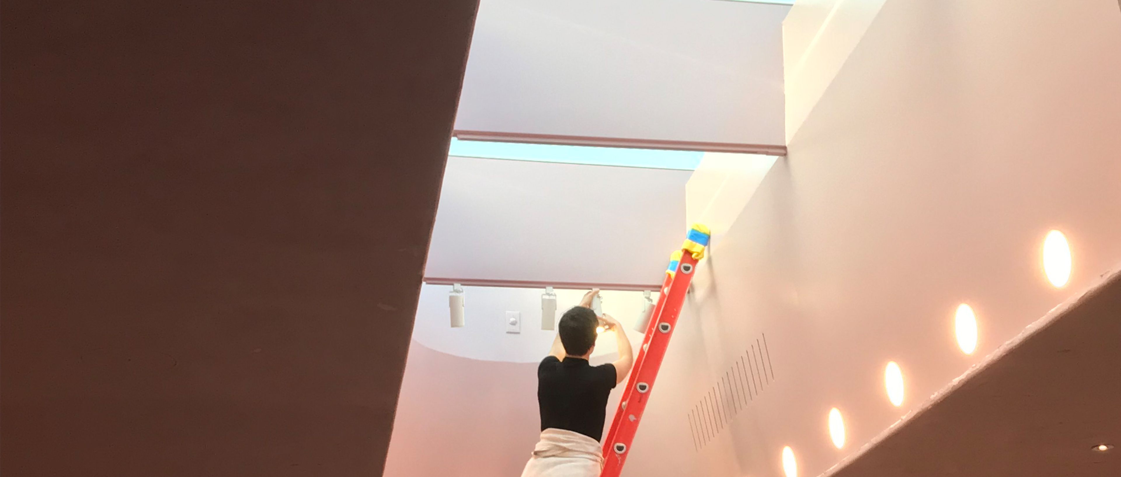 Sara McElroy installing light fixtures